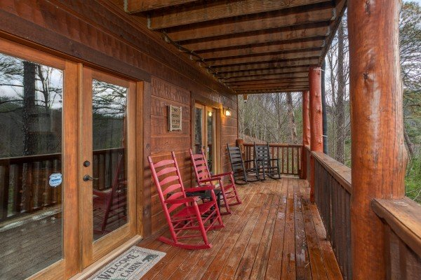 Four rocking chairs in pairs on the covered deck at Black Bear Hide-out, a 3-bedroom cabin rental located in Pigeon Forge