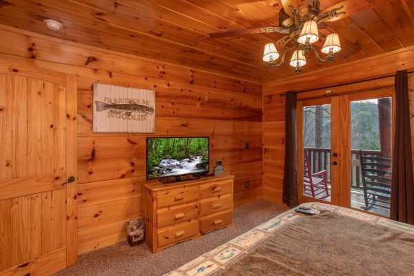 Bedroom with a TV, dresser, and deck access at Black Bear Hide-out, a 3-bedroom cabin rental located in Pigeon Forge