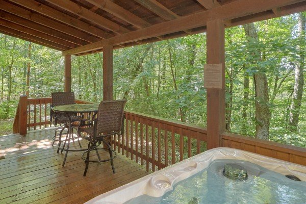 Hot tub on a covered deck with nearby seating at A Place to Remember, a 2 bedroom cabin rental located in Gatlinburg