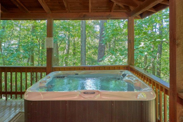 Hot tub on a covered deck with a woods view at A Place to Remember, a 2 bedroom cabin rental located in Gatlinburg