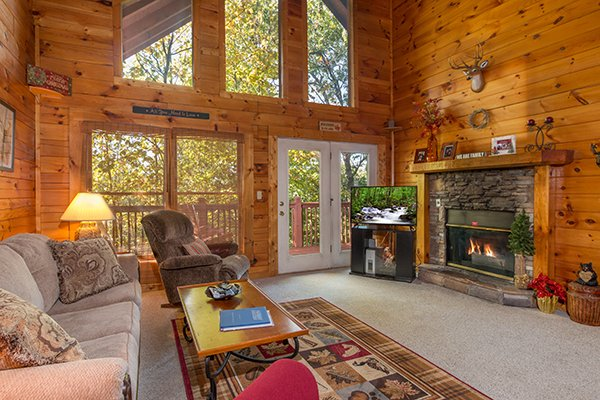 Fireplace with television in the living room at A Honeymoon Haven, a 1 bedroom cabin rental located in Gatlinburg