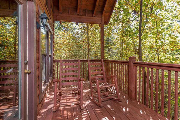 rocking chairs on a deck with woods at a honeymoon haven a 1 bedroom cabin rental located in gatlinburg