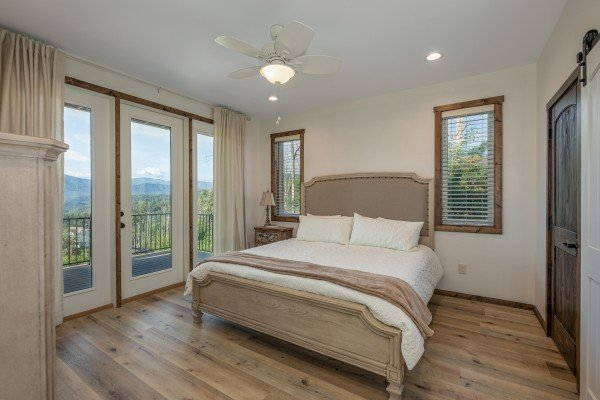 Bedroom with a king bed and night stand at Mountain Celebration, a 4 bedroom cabin rental located in Gatlinburg