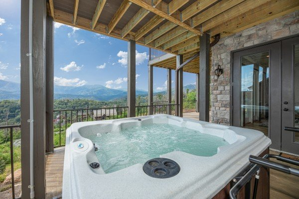 Hot tub on a covered deck at Mountain Celebration, a 4 bedroom cabin rental located in Gatlinburg