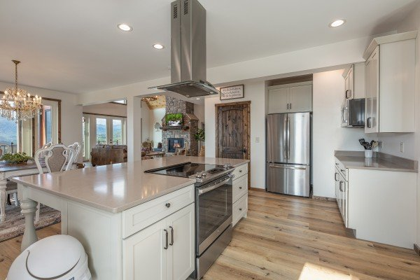 White kitchen with granite counters, stainless appliances, and adjacent dining space at Mountain Celebration, a 4 bedroom cabin rental located in Gatlinburg