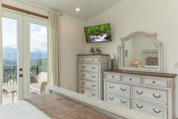 Dresser, chest of drawers, TV, and deck access at Mountain Celebration, a 4 bedroom cabin rental located in Gatlinburg