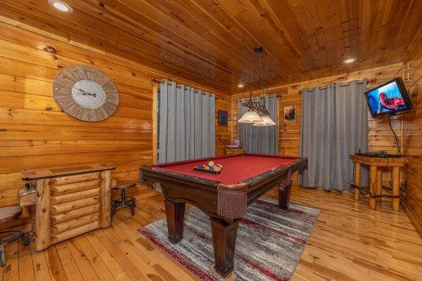 Red felt pool table and TV in a game room at A Bear on the Ridge, a 2 bedroom cabin rental located in Pigeon Forge