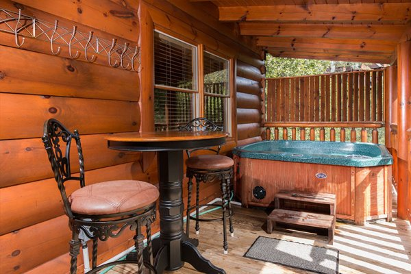 Bar top table with seating for two and hot tub on a covered deck at Bearfoot Memories, a 2-bedroom cabin rental located in Pigeon Forge