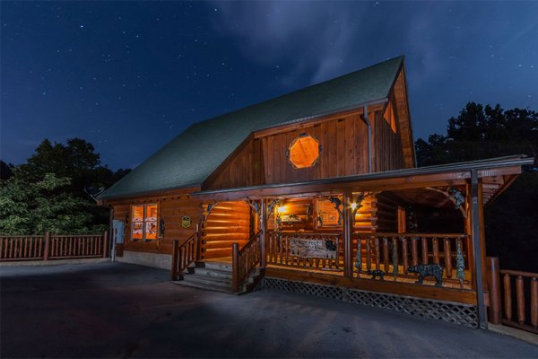 Exterior of cabin lit up at night at Bearfoot Memories, a 2-bedroom cabin rental located in Pigeon Forge