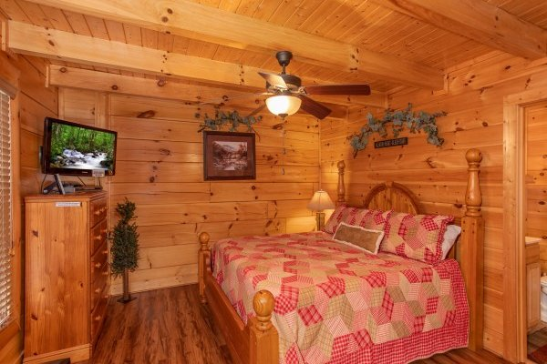 Bedroom with a king-sized bed, dresser, and television at Bearfoot Memories, a 2-bedroom cabin rental located in Pigeon Forge