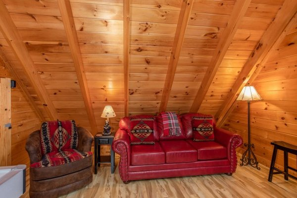 Couch and recliner in the game loft at Bearfoot Memories, a 2-bedroom cabin rental located in Pigeon Forge