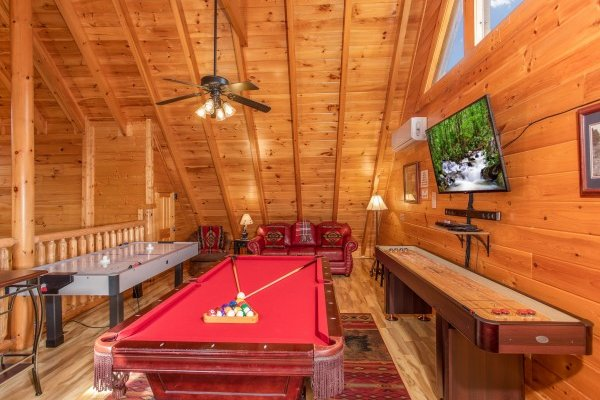 Red felt pool table, air hockey, table, and shuffle board at Bearfoot Memories, a 2-bedroom cabin rental located in Pigeon Forge