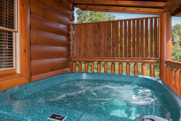 Hot tub on a covered deck with privacy fence at Bearfoot Memories, a 2-bedroom cabin rental located in Pigeon Forge