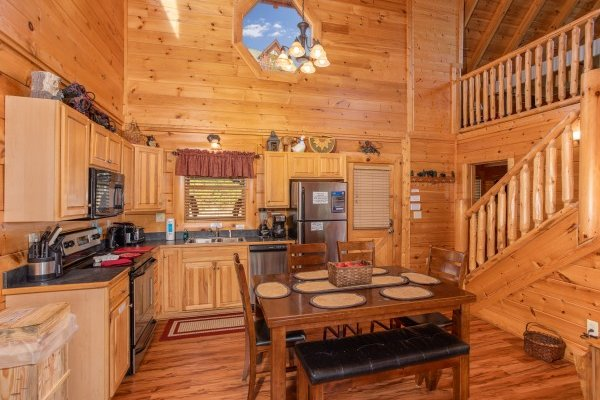 Kitchen with stainless appliances and dining space for six at Bearfoot Memories, a 2-bedroom cabin rental located in Pigeon Forge