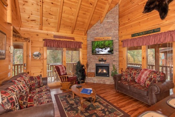Living room with stacked stone fireplace and wall mounted television at Bearfoot Memories, a 2-bedroom cabin rental located in Pigeon Forge