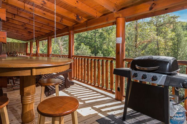 Propane grill and outdoor dining space on a covered deck at Bearfoot Memories, a 2-bedroom cabin rental located in Pigeon Forge