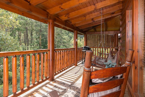 Covered deck with rocker, swing, and grill at Bearfoot Memories, a 2-bedroom cabin rental located in Pigeon Forge
