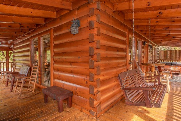 Porch swing on the wraparound covered deck at Bearfoot Memories, a 2-bedroom cabin rental located in Pigeon Forge
