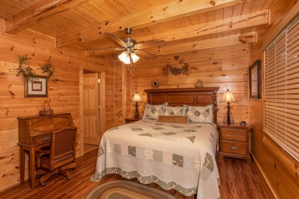 Bedroom with a king-sized bed and writing desk at Bearfoot Memories, a 2-bedroom cabin rental located in Pigeon Forge