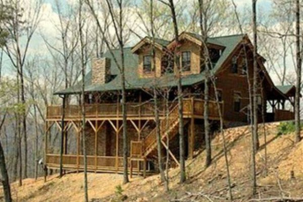 Cabin exterior through the woods at Mystic Ridge, a 4 bedroom cabin rental located in Pigeon Forge