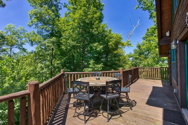 Dining table on the deck at Mystic Ridge, a 4 bedroom cabin rental located in Pigeon Forge
