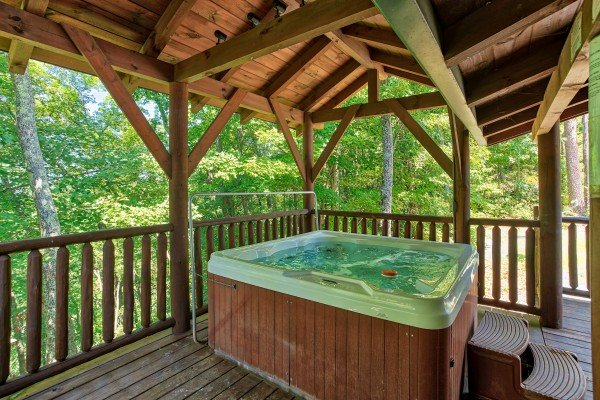 Hot tub on a covered deck at Mystic Ridge, a 4 bedroom cabin rental located in Pigeon Forge