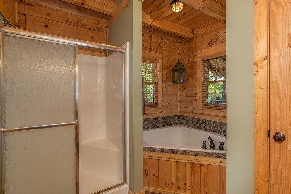 Main floor en suite bath with a jacuzzi tub and separate shower at Mystic Ridge, a 4 bedroom cabin rental located in Pigeon Forge