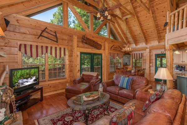 Vaulted living room with a television and deck access at Mystic Ridge, a 4 bedroom cabin rental located in Pigeon Forge