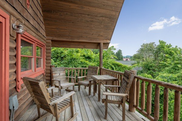 Seating four four with a table on a covered deck at Romantical Rendeviews, a 1 bedroom cabin rental located in Pigeon Forge