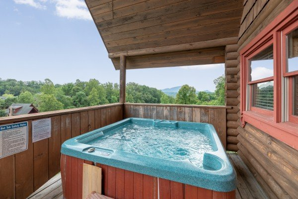 Hot tub on a covered deck at Romantical Rendeviews, a 1 bedroom cabin rental located in Pigeon Forge