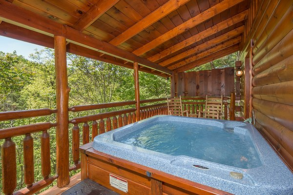 Hot tub on a covered deck with wooded views at Dancing Bearfoot, a 2-bedroom cabin rental located in Pigeon Forge