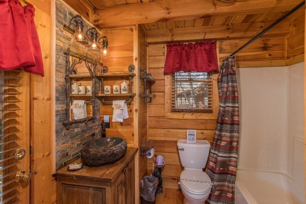 Bathroom with a tub and shower combo and a custom sink and backsplash at Dancing Bearfoot, a 2-bedroom cabin rental located in Pigeon Forge