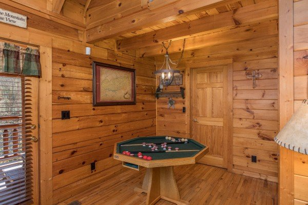 Bumper pool table on the dining table at Dancing Bearfoot, a 2-bedroom cabin rental located in Pigeon Forge
