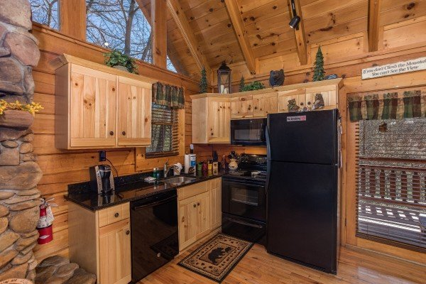 Kitchen with black appliances at Dancing Bearfoot, a 2-bedroom cabin rental located in Pigeon Forge