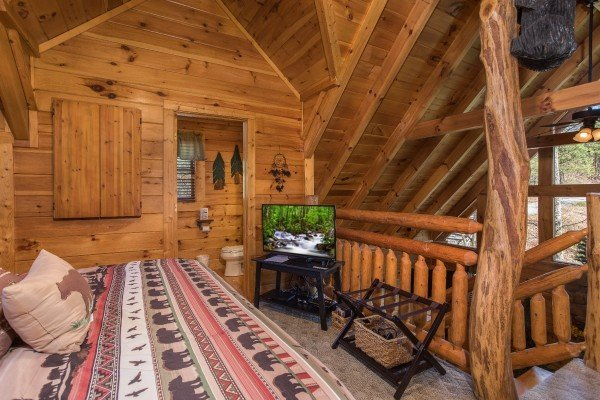 Loft bedroom with a television, suitcase stand, and en suite at Dancing Bearfoot, a 2-bedroom cabin rental located in Pigeon Forge
