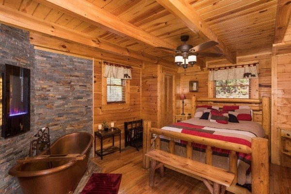 Bedroom with a queen bed and a copper soaking tub at Dancing Bearfoot, a 2-bedroom cabin rental located in Pigeon Forge