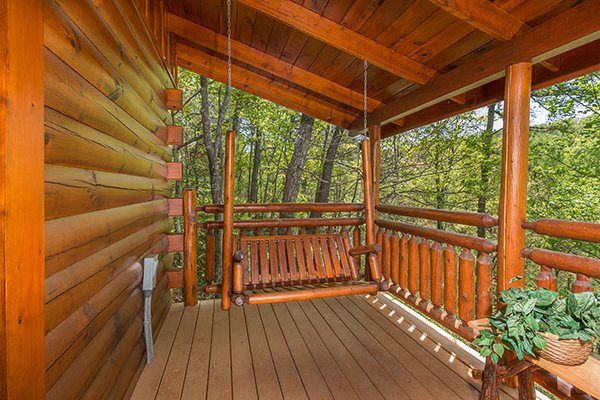 Porch swing on the covered deck at Dancing Bearfoot, a 2-bedroom cabin rental located in Pigeon Forge