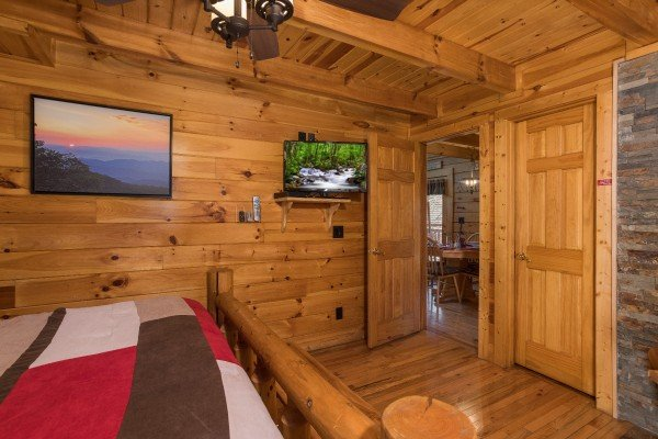 Queen bedroom with a tv, sunset art, and en suite at Dancing Bearfoot, a 2-bedroom cabin rental located in Pigeon Forge