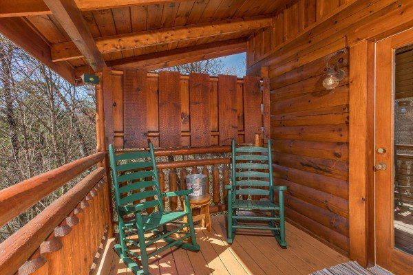 Two rocking chairs by a privacy fence on the covered deck at Dancing Bearfoot, a 2-bedroom cabin rental located in Pigeon Forge