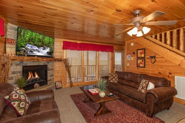 Sofa, fireplace, TV, and deck access from the family room at Better View, a 4 bedroom cabin rental located in Pigeon Forge