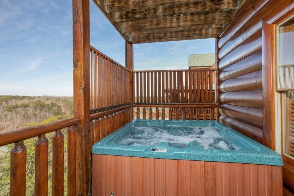 Hot tub on a covered deck at Better View, a 4 bedroom cabin rental located in Pigeon Forge