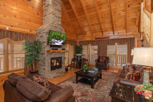 Living room with vaulted ceiling, tall fireplace, and TV at Better View, a 4 bedroom cabin rental located in Pigeon Forge
