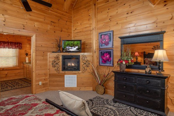 Fireplace, TV, dresser, and en suite bath in the loft bedroom at Better View, a 4 bedroom cabin rental located in Pigeon Forge