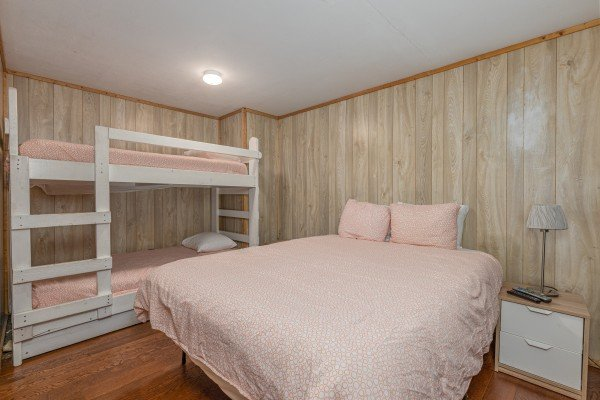 Bedroom with full bed and bunk beds at Terrace Garden Manor, a 13 bedroom cabin rental located in Gatlinburg