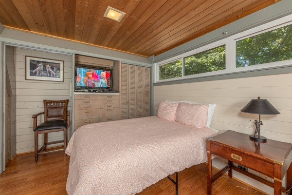 TV and chair in a bedroom at Terrace Garden Manor, a 13 bedroom cabin rental located in Gatlinburg