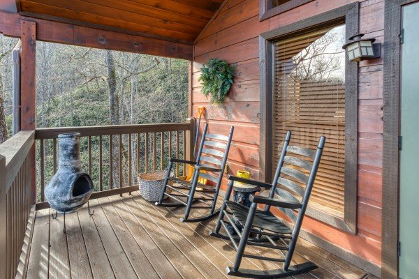 Rocking chairs and a charcoal grill on the covered deck at Secluded View, a 2-bedroom cabin rental in Pigeon Forge