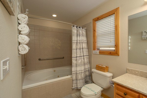 Jacuzzi tub with a shower and custom bear mosaic at Secluded View, a 2-bedroom cabin rental in Pigeon Forge