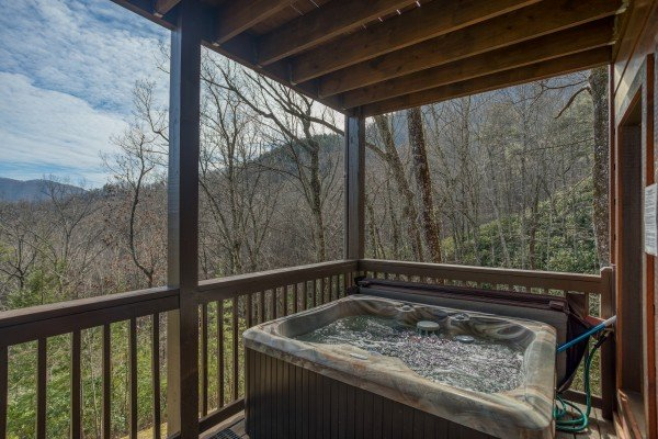 Hot tub on a covered deck at Secluded View, a 2-bedroom cabin rental in Pigeon Forge