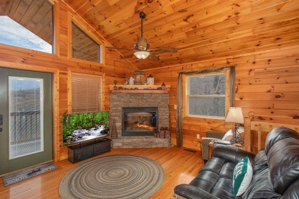 Living room with TV, fireplace, and deck access at Secluded View, a 2-bedroom cabin rental in Pigeon Forge