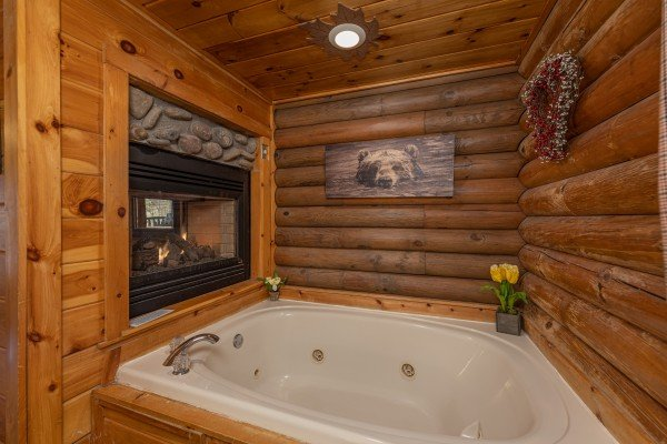 Jacuzzi and a double-sided fireplace at A Lover's Secret, a 1 bedroom cabin rental located in Gatlinburg
